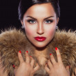 Beautiful brunette holding her hands on fur — Stock Photo