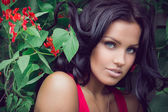 Brunette standing near the bush with red flowers — Stock Photo