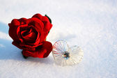 Beatiful red rose in snow with crystal heart in a winter day — Stock Photo