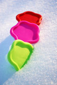 Colored molds green red and pink in the snow in a winter day — Stock Photo