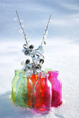 Colored bottles in snow winter day with crystal branches — Stock Photo
