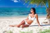The beautiful sexy young girl in bikini on a beach — Stock Photo