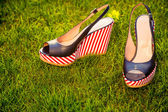 Stylish sandals, lie on the grass in the garden — Stock Photo