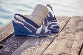 牛仔蓝凉鞋躺在木制的离合器,在湖上 — 图库照片