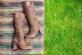Suede boots women lie on the grass — Stock Photo