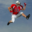 American Football player ball under arm going for it. - Stock Photo