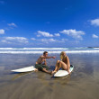 A surfing couple relax on the bach and take in the scenery. - Stock Photo