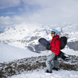 A snowboarder looks out over stunning mountain scape. - Stock Photo