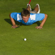 A golfer lining up a put on the green. - Stockfoto