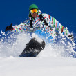 A snowboarder riding hard through the fresh powder snow smiles. - Zdjęcie stockowe