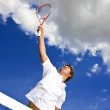 A tennis player stretches high above the net. - Zdjęcie stockowe