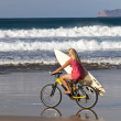 Surfer girl rides to the Ocean waves on mountain bike. - Stockfoto