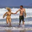 A young couple running in the surf. - Stockfoto