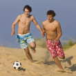 Two beach soccer players competing for the ball. - Zdjęcie stockowe