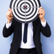 Businessman holding dartboard — Stock Photo