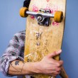 Skater hiding behind his skateboard — Stock Photo