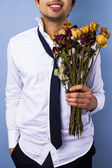 Young man with withered flowers — Stock Photo