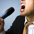 Businessman singing karaoke — ストック写真