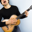 Happy man playing acoustic guitar — Stock Photo