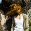 Young woman in tree with windblown hair — Stock Photo