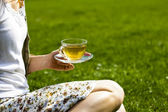 Young woman drinking tea in the park — Stock Photo