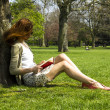 Young woman reading in park - Stockfoto