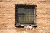 Grunge wired up window and brick wall — Stock Photo