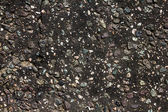 çakıl taşları ve çatlaklar ile koyu kaya arka plan — Stok fotoğraf