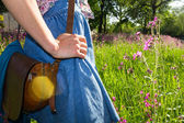Mujer joven con pie bolso vintage en campo — Stockfoto