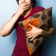 Young man clutching cushion while watching scary movie — 图库照片
