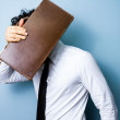 Businessman hiding his face behind an old briefcase — Stock Photo