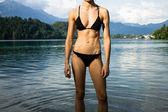Woman in bikini relaxing in a mountain lake — Stock Photo