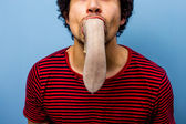 Man with a cow's tongue in his mouth — Stock Photo