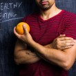 Fit man holding a grapefruit in front of blackboard — Stock Photo