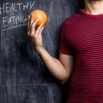 man att främja sunda kostvanor framför svarta tavlan — Stockfoto
