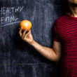 Man promoting healthy eating in front of blackboard — Stock Photo
