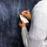 Man taking notes by blackboard — Stock Photo #28971627