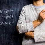 Teacher standing by blackboard — Stock Photo