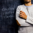 Teacher standing by blackboard — Stock Photo