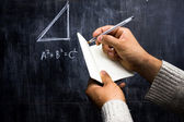 Man taking notes of math theorem on blackboard — Stock Photo