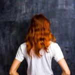 Redhead woman by blank blackboard — Stock Photo #29176811