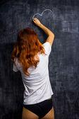Mujer pelirroja en ropa interior en una pizarra de dibujo — Foto de Stock