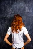 Redhead woman by blank blackboard — Stock Photo