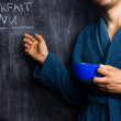 Man in robe pointing at breakfast menu on blackboard — Stock Photo