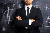 Successful businessman posing in front of dollar signs — Stock Photo