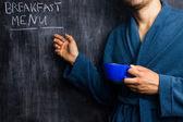 Człowiek w szaty, wskazując w menu śniadanie tablica — Zdjęcie stockowe