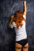 Redhead woman in underwear drawing on a blackboard — Stock Photo