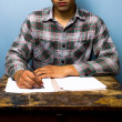 Young man writing at desk — Stockfoto