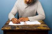 Young man writing at desk — Stock Photo