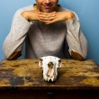 Smirking man with skull at desk — Stock Photo